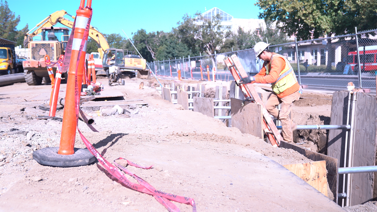 Image of construction site on the UC Davis campus showing a man coming out of a trench using a ladder.